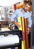 Male advertising studio worker with rolls of colored paper standing royalty free stock images