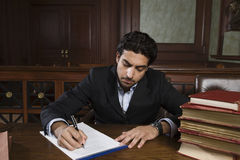 Male Advocate Preparing Notes. Male advocate with law books preparing notes in courtroom Royalty Free Stock Photos