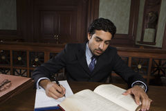 Male Advocate Reading Law Book. Male advocate reading book for reference while preparing notes Stock Images