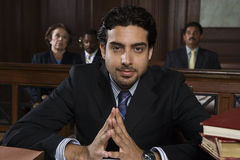 Male Advocate Sitting In Courtroom. Portrait of a confident male advocate sitting with people in the courtroom Stock Photography