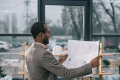 Male african american architect looking at building plan. In modern office stock images