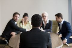 Male African American job candidate applying for position in off. Back view of male African American job candidate recruit for position in office, HR team stock images