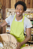 Male African American store clerk holding basket of peanuts Stock Images