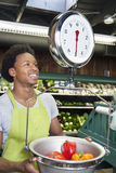 Male African American store clerk weighing bell peppers on scale Royalty Free Stock Photography