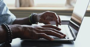 Male african american user typing on laptop at table, closeup