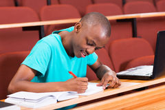 Male african college student. Handsome male african college student writing classwork Royalty Free Stock Image