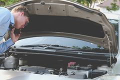 Male agent examining engine for claiming auto insurance. caucasi. An man calling for assistance for car broken down by traffic accident Royalty Free Stock Photography