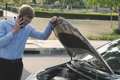 Male agent examining engine for claiming auto insurance. caucasi. An man calling for assistance for car broken down by traffic accident Royalty Free Stock Images