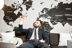 Male agent relaxing at the travel agency office. Handsome male agent playing with toy airplane at the travel agency office with world map on the background Royalty Free Stock Photo