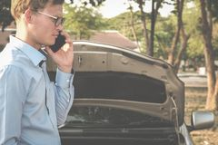 Male agent use smart phone for claiming auto insurance. caucasia. N man calling for assistance for car damaged by traffic accident Royalty Free Stock Photography