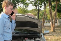 Male agent use smart phone for claiming auto insurance. caucasia. N man calling for assistance for car damaged by traffic accident Stock Photo