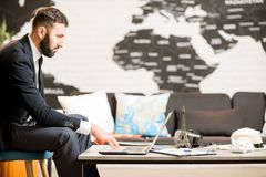 Male agent working at the travel agency office. Handsome male agent working with laptop at the travel agency office with map on the background Royalty Free Stock Images