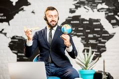 Male agent working at the travel agency office. Handsome male agent playing with globe and toy airplane at the travel agency office with world map on the Royalty Free Stock Image