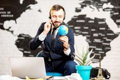 Male agent working at the travel agency office. Handsome male agent working with globe and headset sitting at the travel agency office with world map on the Royalty Free Stock Photos