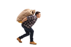 Male agricultural worker carrying burlap sack on his back Stock Image