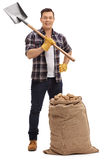 Male agricultural worker posing with shovel and burlap sack Stock Photo