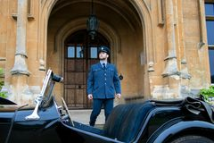 Male AIR Force Officer Pilot in uniform leaves Britiish mansion and climbs into his vintage sports car stock photo