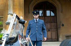 Male AIR Force Officer Pilot in uniform leaves Britiish mansion and climbs into his vintage sports car. Handsome WWII, Air force corporal in blue uniform leaves royalty free stock images