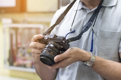 Male amateur photographer taking focusing to make photos in cont. Rol room,Young man taking pictures for relaxing on vintage camera Royalty Free Stock Image