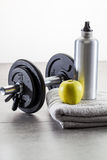 Male ambiance at the gym with dumbbells and aluminium bottle. Male ambiance at the gym with dumbbells, aluminium bottle and an healthy apple set on a grey towel Royalty Free Stock Images