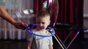 The male animator put a soap bubble on the little boy`s head. The bubble dissolved. stock footage