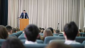 Male announcer conducts a seminar in the hall. Lot of people sitting at a seminar lectures and conferences. Listen to the speaker stock video