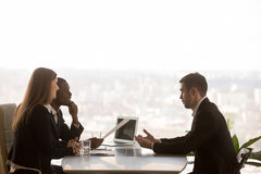 Male applicant and multi-ethnic recruiters during job interview,. Friendly attentive hr managers interviewing vacancy applicant, multi-ethnic partners discussing Royalty Free Stock Photography