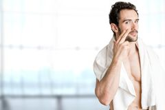 Male Skin Care. Male applying moisturizer to her face in a bathroom Royalty Free Stock Image