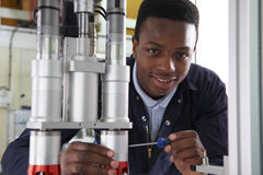 Male Apprentice Engineer Working On Machine In Factory Stock Image
