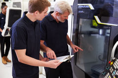 Male Apprentice Working With Engineer On CNC Machinery Stock Image