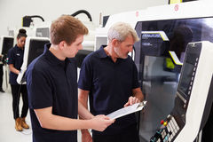 Male Apprentice Working With Engineer On CNC Machinery Royalty Free Stock Photo