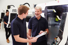 Male Apprentice Working With Engineer On CNC Machinery Royalty Free Stock Photos