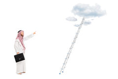 Male arab person with briefcase standing in front of a ladder wi Stock Image