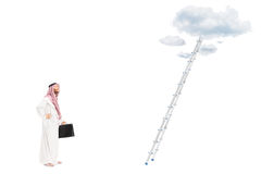 Male arab person standing in front of ladder royalty free stock image