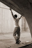 Male in Arch. Slim male model in concrete arch. arms are outstretched he's wearing jeans a white tank top and boots. model has spikey hair and looks to be Stock Photo