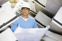 Male architect with blueprint working at construction site Stock Photo