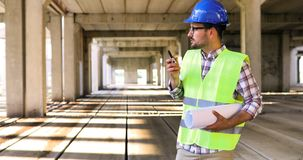 Male architect with blueprints using walkie-talkie. At construction site Stock Image