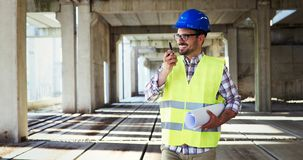 Male architect with blueprints using walkie-talkie. At construction site Royalty Free Stock Photo