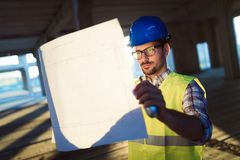 Male young architect with blueprints using walkie-talkie. Male architect with blueprints using walkie-talkie at construction site stock photos