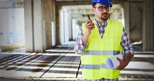 Male architect with blueprints using walkie-talkie. At construction site Royalty Free Stock Photos