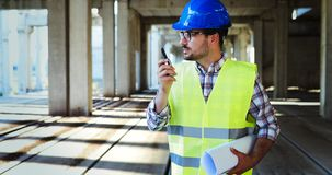 Male architect with blueprints using walkie-talkie. At construction site Royalty Free Stock Image