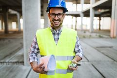 Male architect with blueprints using walkie-talkie. At construction site Stock Images