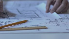 Male architect checking building layout, making notes and calculations, design