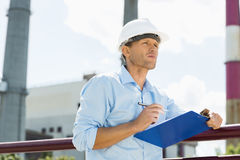 Male architect with clipboard and pen at site Royalty Free Stock Image
