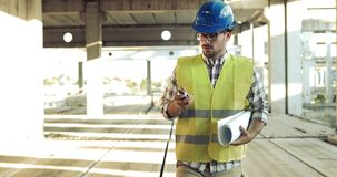 Male architect communicating on walkie-talkie at site. Male architect communicating on walkie-talkie at building site Stock Photo