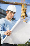 Male architect examining blueprint at construction site Stock Images