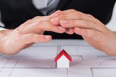 Male Architect Hand Sheltering House Model Stock Photo