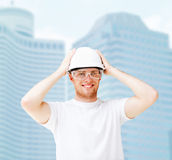 Male architect in helmet with safety glasses. Building, developing, consrtuction and architecture concept - picture of male architect in white helmet with safety Stock Images