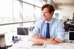 Male architect at his desk in an office, looking away Stock Image
