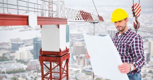 Male architect holding blue print by crane at construction site Royalty Free Stock Photos